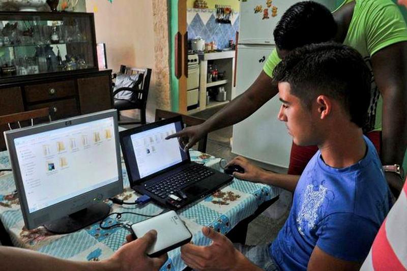 Jóvenes preparan discos portátiles y unidades USB con películas, series de televisión, noticias y otra información, en abril del 2014 en La Habana. Solo el 3.4% de la población tiene conexiones privadas de internet. STR AFP/Getty Images