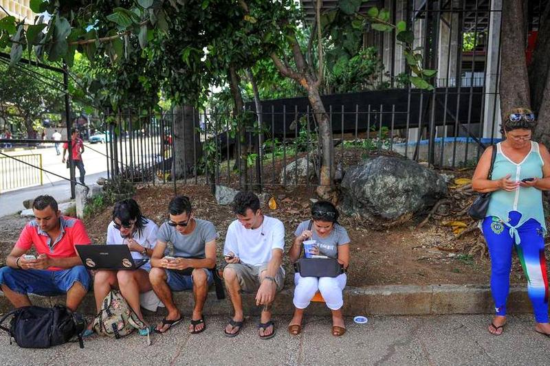 Cubanos usan dispositivos móviles para conectarse vía Wi-Fi en La Habana. Etecsa, la empresa de telecomunicaciones del estado, abrió 35 áreas Wi-Fi en el país y redujo las tarifas de conexión a la mitad del precio en un esfuerzo por ampliar la limitada conectividad de la isla. YAMIL LAGE AFP/Getty Images